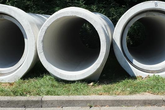 Kanalrohre liegen montagebereit am Straßenrand in Kleinenbroich