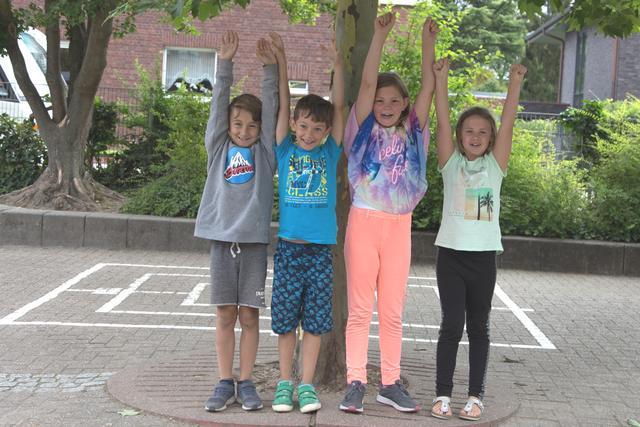 Vier Grundschulkinder stehen unter einem Baum und strecken lachend die Arme hoch