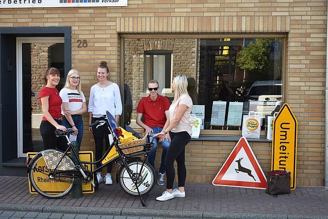 Junge Menschen stehen mit einem Fahrrad und Verkehrsschilder vor einem Schaufenster