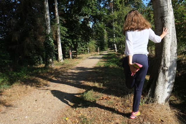 Joggerin lehnt sich zum Beine dehnen an eine Birke Höhe Sportplatz Liedberg