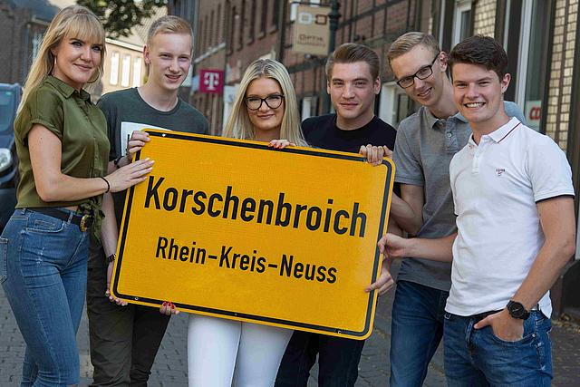 Azubis mit dem Ortsschild von Korschenbroich