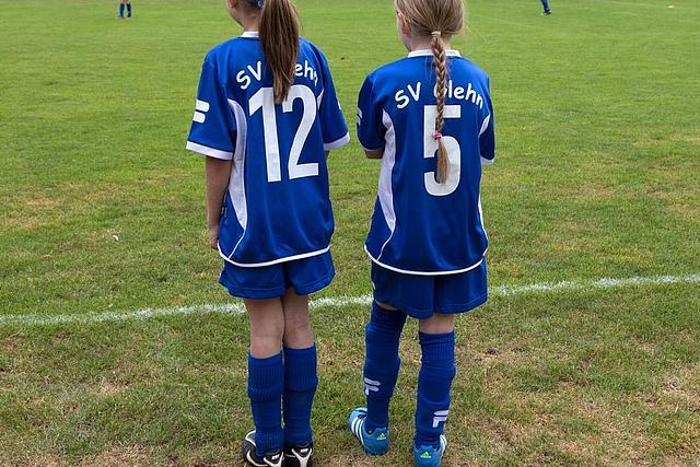 Rückenansicht: zwei junge Fußballspielerinnen stehen am Spielfeldrand und tragen das Trikot vom SV Glehn