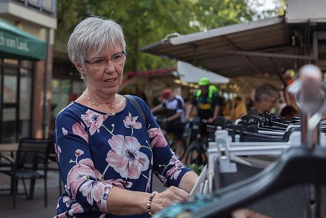 Dame in geblümter Bluse an einem Kleiderständer auf dem Kleinenbroicher Wochenmarkt