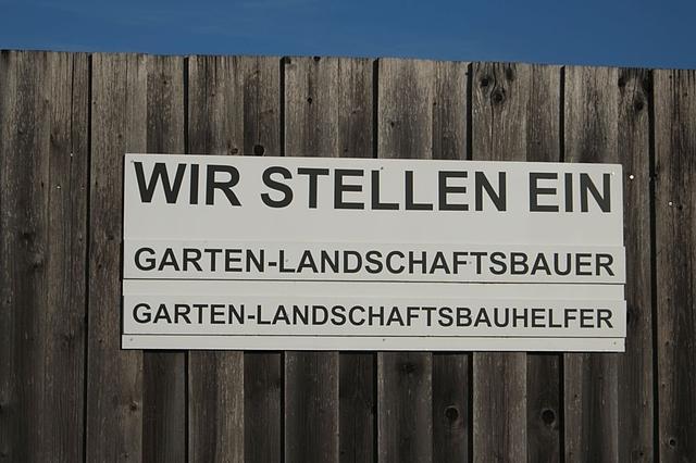 Schild vor Holzzaun mit Text Wir stellen ein