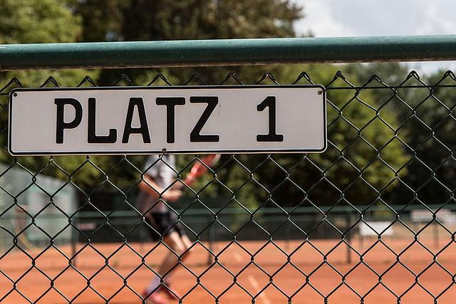 """Tennisplatz Nahaufnahme des Schildes """"Platz 1"""", im Hintergrund ist ein Tennisspieler zu erkennen"""
