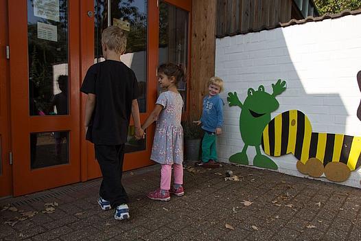 Außenansicht Eingangsbereich der KiTa Auf den Kempen, zwei Kinder gehen hinein