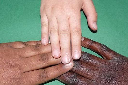 drei Kinderhände miteinander verbunden