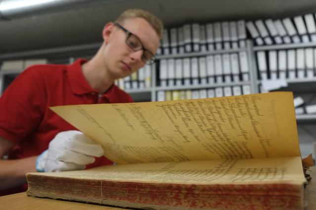 Mann mit Handschuh blättert in Archivunterlagen