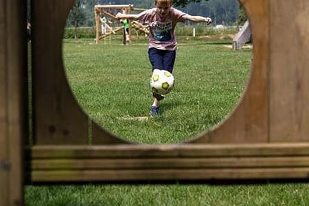 Blick durch die Ballöffnung Torwand: Kind schießt mit einem Fußball auf eine Torwand