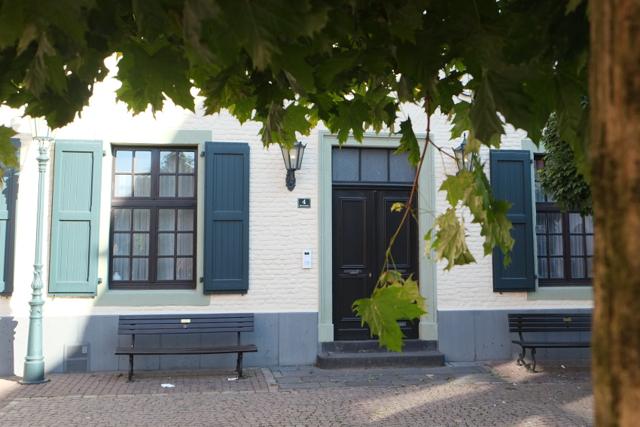 Hannen-Stammhaus im Sommer hinter belaubter Platane
