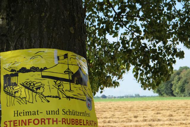 An Baum geklebtes Festplakat Steinforth mit Dorf im Hintergrund