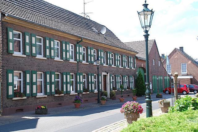 Außenansicht: Der Birkhof, ein langes Backsteingebäude mit grün-weißen Fensterläden, gelegen an einer ruhigen Straße.