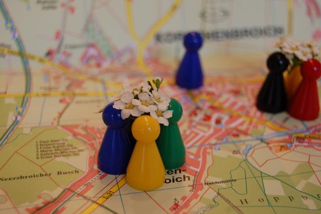 Bunte blumenbekrönte Spielfiguren stehen auf dem Stadtplan eng zusammen