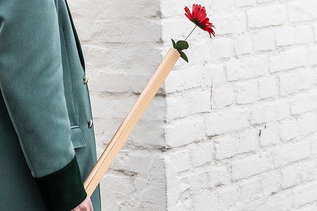 Detailnahme eines Holzgewehres mit Blume im Lauf