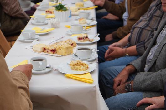 Detailaufnahme: Ältere Menschen sitzen an gedeckter Kaffeetafel