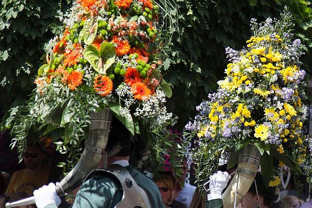 Ein Schützenfest-Umzug. Im Vordergrund tragen Personen Blasintrumente, die mit großen Blumengebinden bestückt sind.