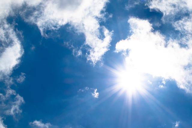 Sonne blitzt durch Wolken vom strahlend blauen Himmel