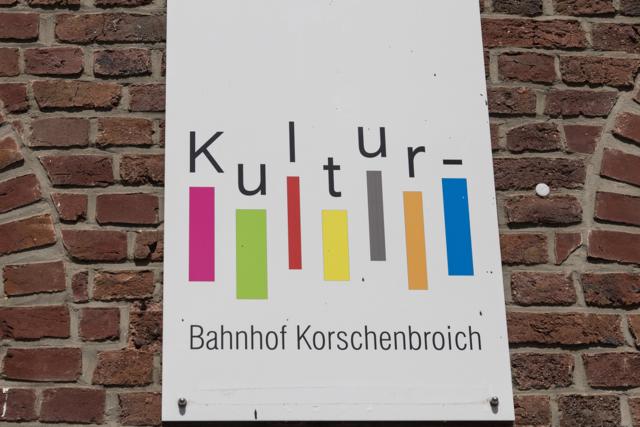 Detailansicht: Schild mit Kulturbahnhof-Logo auf der Bachsteinmauer