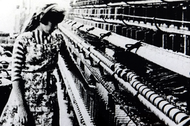 Mitarbeiterin der Textilfabrik Irmen am Webstuhl