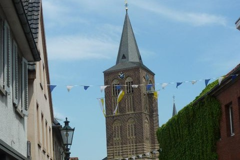 Blick in eine Straße. Im Hintergrund ist eine Kirche zu sehen. Quelle: Wikipedia.