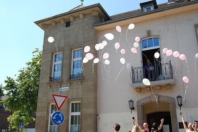 Außenansicht altes Rathaus Korschenbroich. Personen lassen rosafarbene Luftballons in die Luft steigen.