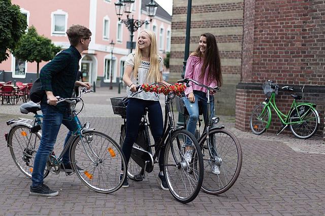 Ein Junge und zwei Mädchen auf Fahrrädern. Sie stehen auf einem Platz, unterhalten sich und haben Spaß.