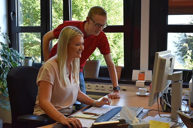 Eine Auszubildende und ein Auszubildender am Schreibtisch bei der Arbeit.