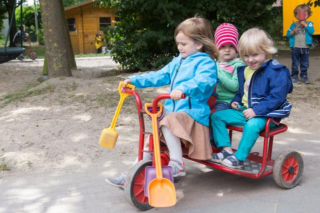 Drei Mädchen fahren auf einem Rollermobil durch das Außengelände der Kita Danziger Straße