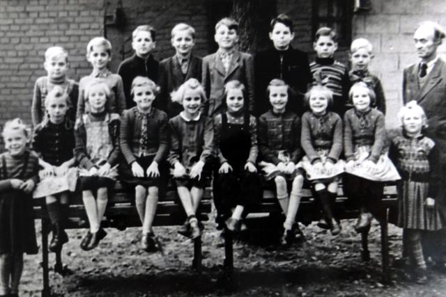 Schüukinder zum Klassenfoto aufgestellt mit dem Lehrer rechts im Bild