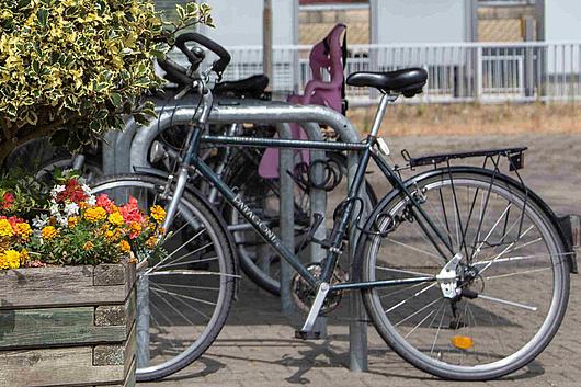 Der Bahnhofsvorplatz in Kleinenbroich: Radständer mit Fahrrädern und im Vordergrund ein Blumenkübel
