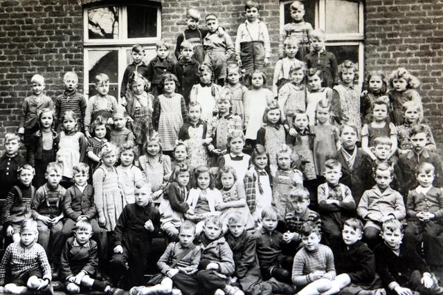 Schulkinder vor einem Backsteingebäude aufgereiht