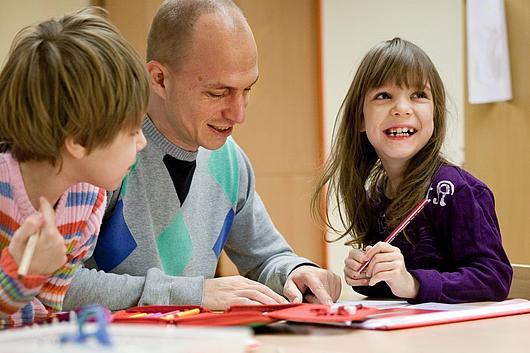 Ein Bufdi mit zwei Kinder in der Hausaufgabenbetreuung