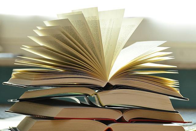 vier Bücher liegen geöffnet übereinander, das oberste Buch ist aufgeschlagen