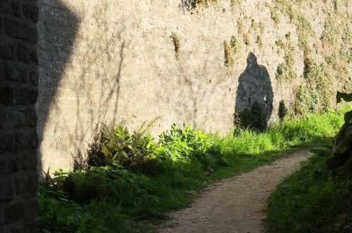 Schatten eines Wanderers hinter dem Torbogen