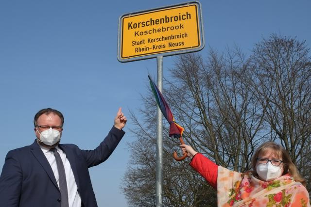 Marc Venten und Barbara Romann zeigen auf das neue Schild in Korschenbroich