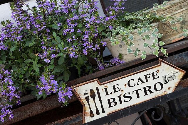 """Nahaufnahme: Ein antikes Metallschild mit der Aufschrift """"Le Cafe Bistro"""", an einem Metallgelände befestigt. Oberhalb des Geländes stehen Blumenkästen mit Blumen."""