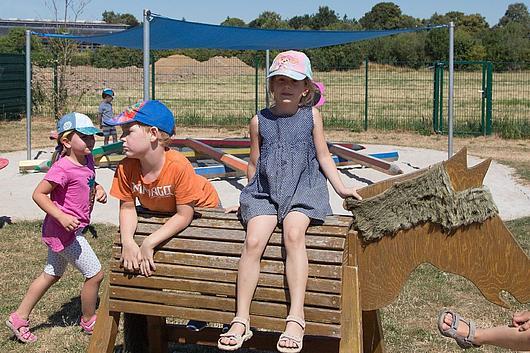 Ein Mädchen sitzt auf einem Pferd aus Holz. Im Hintergrund weitere Kinder und eine große Sandfläche.
