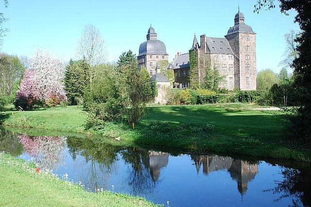 Schloss Myllendonk inmitten grüner Wiesen und umgeben von einem Wassergraben.
