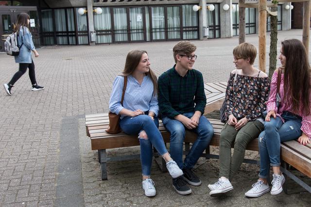 Vier Abiturienten unterhalten sich auf der Bank sitzend vor dem GyKo