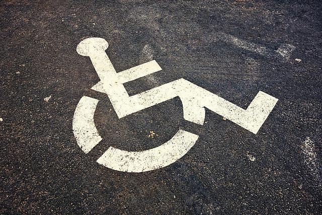 Symbol Rollstuhl auf Asphalt