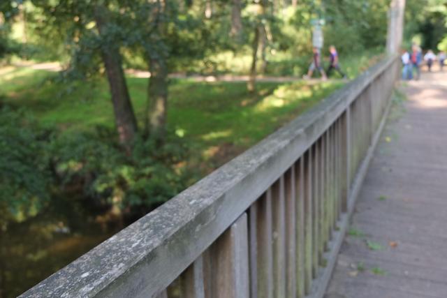Brückengeländer in Neesbroich, fünf Walkerinnen biegen im Hintergrund ab