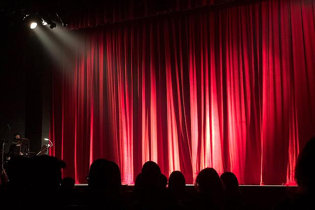 Publikum sitzt im Dunklen vor einem angestrahlten roten Vorhang