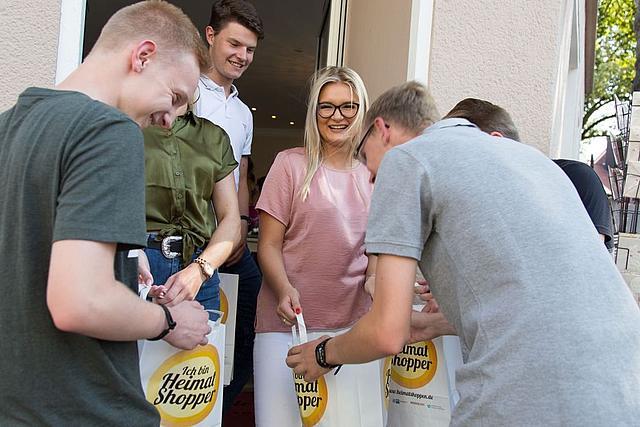 Junge Leute schauen vor einem Geschäftseingang in ihre Papiertüten mit dem Aufdruck Heimat shoppen