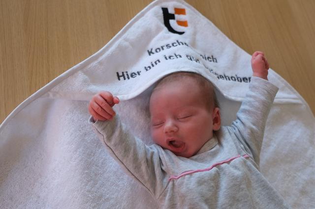 Baby streckt sich im Kapuzenhandtuch mit der Aufschrift Korschenbroich hier bin ich gut aufgehoben