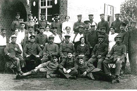 Gruppenfoto: Soldaten und Pflegerinnen vor einem Lazarett.