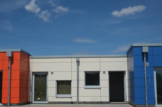 Neubaudetail, weißer Baukörper eingeramt von hervorspringenden Gruppenräumen, orange und blau