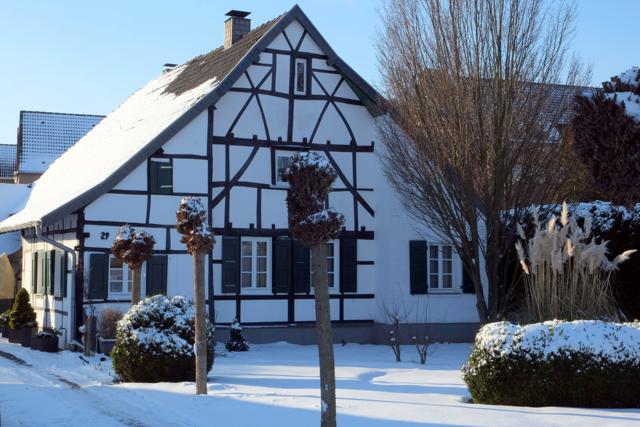 Kleinenbroicher Fachwerkhaus hinter schneebedecktem Vorgarten