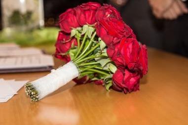Brautstrauß aus Rosen liegt auf einem Tisch.
