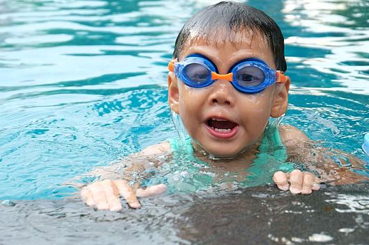 Kind mit Taucherbrille am Beckenrand