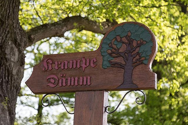 """Ein Schild aus Holz mit der Aufschrift """"Krampe Dämm""""."""